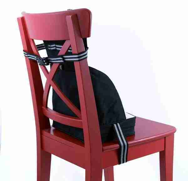 The booster seat attaches to the chair with 2 straps